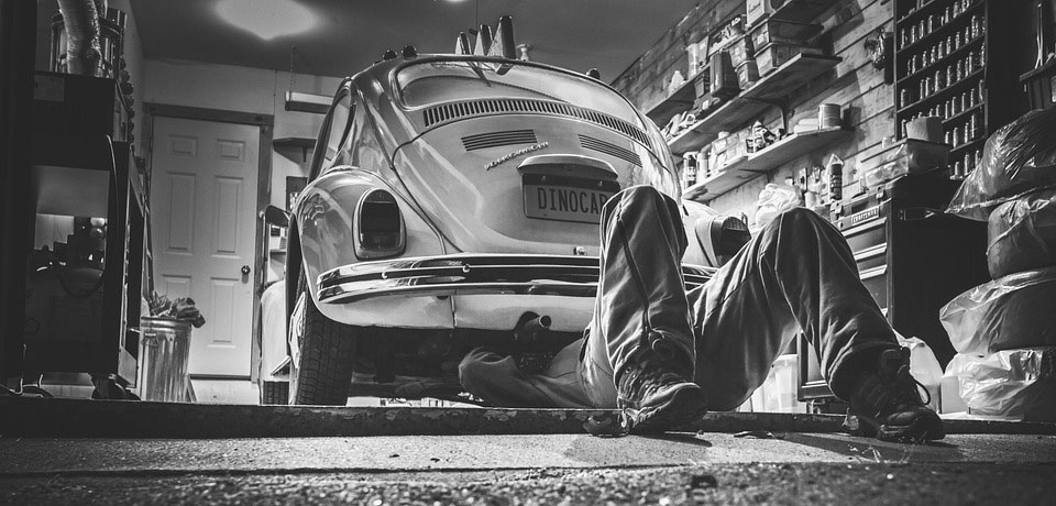 Man working under old volkswagon beetle