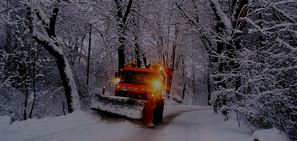 snow plow on street at night