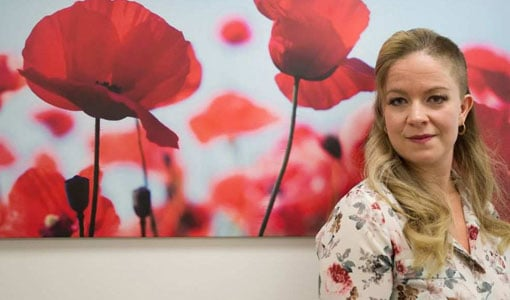 Angela Ayre in front of poppy image
