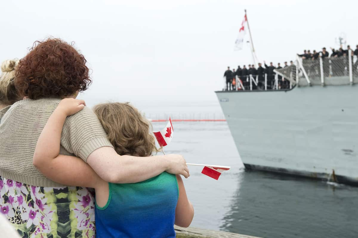 military family watching canadian naval ship depart